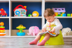 Toddler`s first days on the potty. Happy female toddler sitting on the potty and reading book Stock Photos