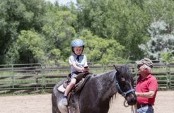 Toddler with a Safety Helmet on Goes on a Pony Ride at a Local Farm with his Horse Being Led Grandfather royalty free stock photography