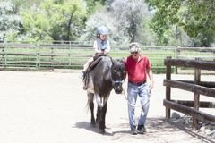 Toddler with a Safety Helmet on Goes on a Pony Ride at a Local Farm with his Horse Being Led Grandfather royalty free stock photos