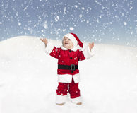 Toddler in santa claus outfit standing in the snow ,  looking up Royalty Free Stock Photo