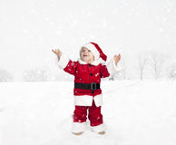 Toddler in santa claus outfit standing in the snow ,  looking up Royalty Free Stock Photography