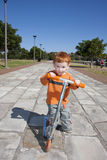 Toddler on Scooter in park. Young boy on scooter on path in park Stock Images