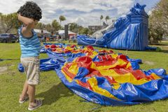 A toddler scratches his head while he stands next to a deflated bounce house. The local park holds a community festival filled with bounce house`s for the kids stock images