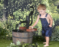 Toddler Scrubbing Bricks by the Water Pump stock images