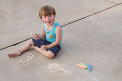 Toddler with sidewalk chalk. A three-year old sidewalk chalk artist sits on a light colored pavement. Space at the side for text copy Stock Image