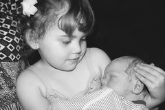 Toddler sister holding her newborn brother black and white royalty free stock photo