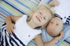Toddler Sister Laying Next to Her Baby Brother on Blanket Royalty Free Stock Image