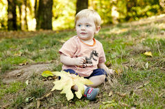 Toddler sits on the grass at the park Royalty Free Stock Image