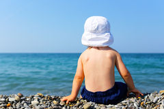 Toddler sits on stone beach Royalty Free Stock Image