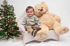 Toddler sits by teddy bear and Christmas tree Stock Photography