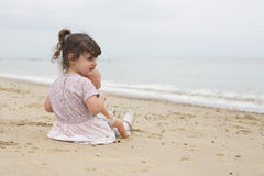 Toddler sitting on beach with her dolly stock photo