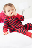 Toddler Sitting On Bed Wearing Pajamas Stock Image