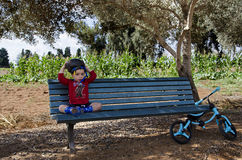 Toddler sitting on a bench holding his bicycle helmet Royalty Free Stock Photography