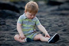 Toddler sitting on black sand beach Stock Images