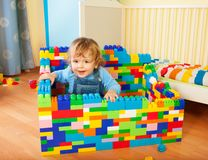 Toddler sitting a castle of toy blocks royalty free stock image