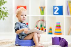 Toddler sitting on chamber pot playing tablet pc Stock Images