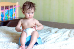 Toddler sitting on chamber pot in the room royalty free stock photography