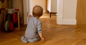 Toddler sitting by doorway. Toddler opens and closes the door. Back view of little baby in striped romper closing room door while sitting on floor in daylight stock video footage