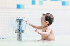 Toddler sitting in front of little fountain. Royalty Free Stock Photo