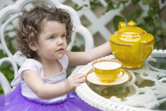 Toddler sitting in garden with teapot Stock Photo