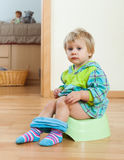 Toddler sitting on green potty Royalty Free Stock Image