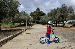Toddler sitting on his balance bicycle Stock Photography