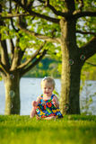 Toddler sitting outside playing with bubbles stock images
