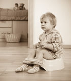 Toddler sitting on potty. Toddler sitting on green potty stock photos