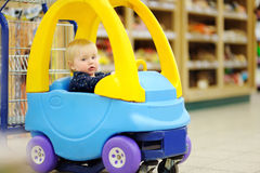 Toddler sitting in the shopping cart Royalty Free Stock Photos