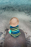 Toddler sitting on small stone pier with shallow sea water Stock Photos