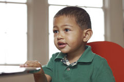 Toddler sitting at a table. Head and shoulders of mixed race infant sitting in a room Royalty Free Stock Images