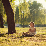 Toddler sitting under the tree Royalty Free Stock Photography
