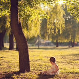 Toddler sitting under the tree Stock Photo
