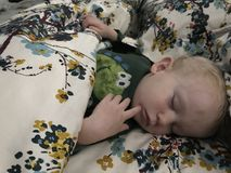 Toddler sleeping. Cute toddler sleeping in his parents bed stock photography