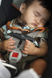 Toddler sleeping in safety chair Stock Photo