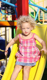 Toddler on a slide. A caucasian toddler with electric blue eyes going down a slide Royalty Free Stock Photo