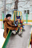 Toddler on slide. Toddler is sitting on the slide in winter Royalty Free Stock Photography