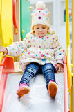 Toddler on slide. Cute toddler on slide on the playground Royalty Free Stock Photos