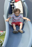 Toddler on a slide. The toddler is on a slide at outdoor playground Stock Photos