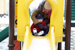 Toddler on slide. Toddler on a slide at playground in winter Stock Photography