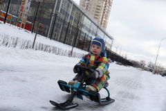 Toddler slides on snow scooter Royalty Free Stock Images