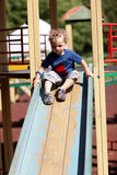 Toddler sliding on a slide Stock Image