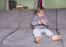 Toddler with smartphone. Little boy using a mobile phone sitting on the couch Stock Photos