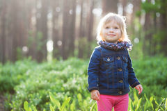 Toddler smiling girl in forest. Cute smiling girl in forest with sun backlight Stock Images