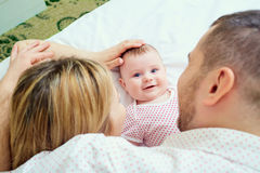 Toddler smiling next to his mother and father lying on the bed Stock Image