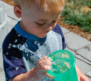 Child Spills Water Slow Motion. Water droplets spill in slow motion from the toddler`s drinking cup on a hot summer day royalty free stock image