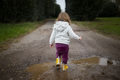 Toddler splashing in puddle in country road stock photos