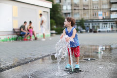 Toddler and a splashing water fountain Stock Photography