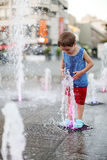 Toddler and a splashing water fountain Stock Photos