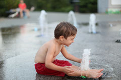 Toddler and a splashing water fountain Stock Photo